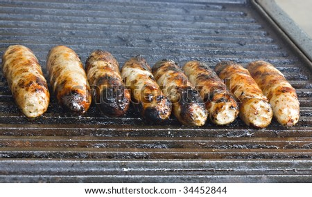 A row of sausages cooking on a barbecue - stock photo