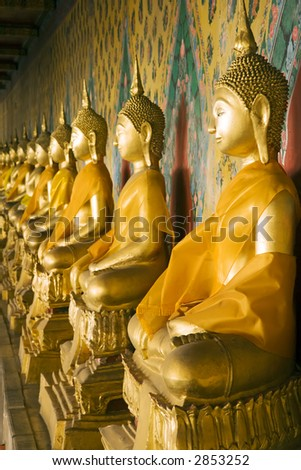 A row of seated Buddhas at the temple of Wat Arun in Bangkok, Thailand. (Focus on far right Buddha.) - stock photo