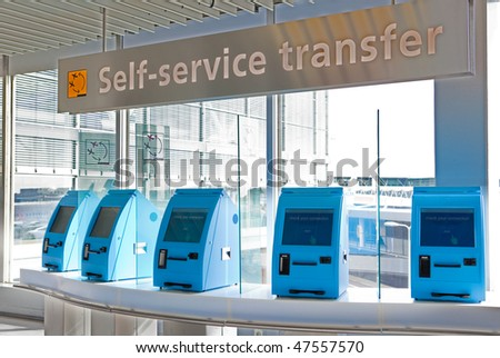 A row of self service check in machines in an airport - stock photo