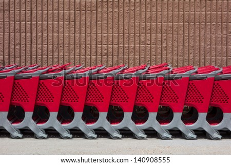 A row of shopping carts against a wall - stock photo