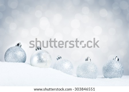 A row of silver Christmas baubles on snow with defocused silver and white lights in the background. Shallow depth of field. - stock photo