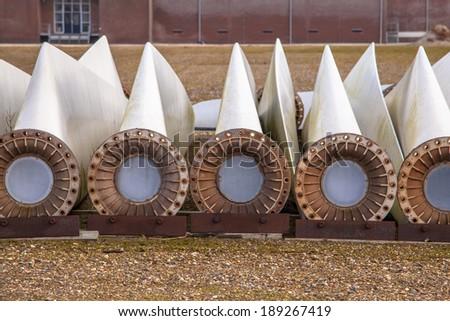 A row of spare wind turbine blades on wins turbine maintenance yard - stock photo
