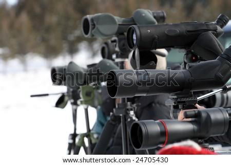 A row of spotting telescopes on tripods. - stock photo