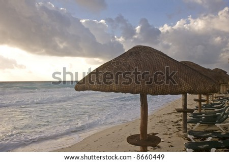 A row of straw and wooden umbrellas providing shelter on a beach - stock photo