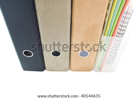 A row of suede lever arch ring binders - black, tan and faun and a clear plastic magazine rack containing cardboard files in blue; green; orange; yellow; white plus spiral bound notebook. - stock photo