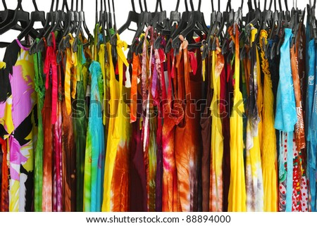 A row of summer clothes hanging on the rack - stock photo