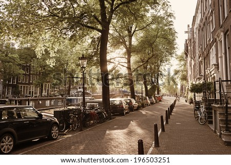 A row of terraced houses with cars parked on the opposite side of the road. - stock photo