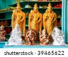 A row of three golden seated Buddhas statue souvenirs on a shelf - stock photo