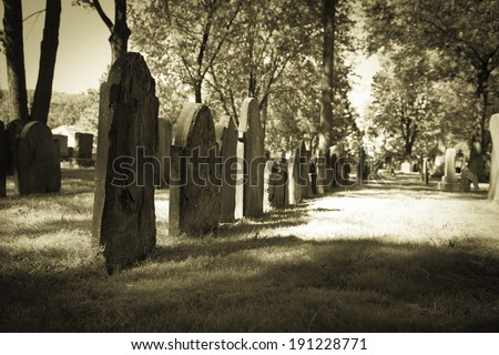 A row of tombstones in a very old cemetery; photo done in halloween or seasonal colortones - stock photo