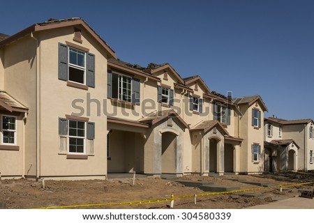 A row of townhomes in the final stages of construction, soon to be ready for sale. - stock photo