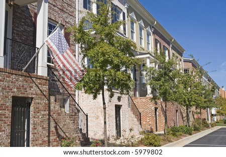 A row of townhouses with an American flag out front - stock photo