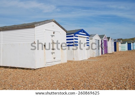 A row of traditional British beach huts on the pebble beach at Glyne Gap between Hastings and Bexhill-on-Sea in East Sussex, England.