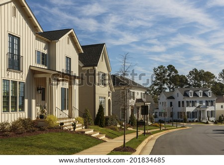 A row of upscale houses on a curved neighborhood street on a sunny day. Foreground house features a french balcony. Background house is multi-level. Also seen are trees, yards, and steps. - stock photo