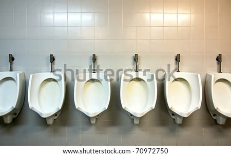 A row of urinals in tiled wall in a public restroom - stock photo