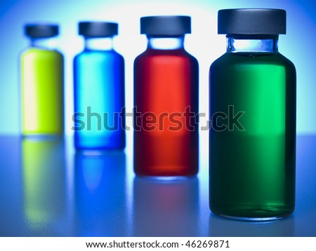A row of vials filled with colored liquids. Focus on the green one. - stock photo