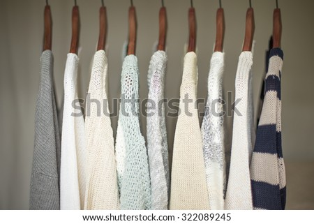 A row of warm and soft sweaters for women on wooden hangers in a closet. - stock photo