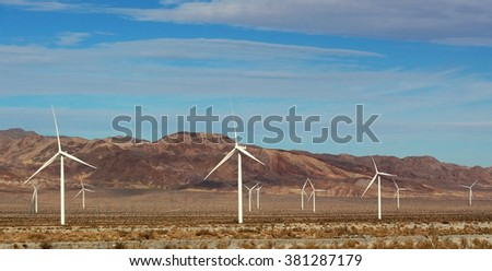 A row of wind turbines in the desert - stock photo