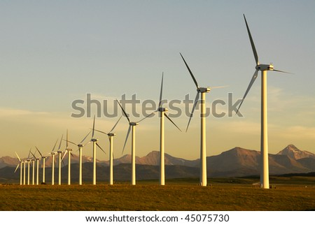 A row of windmills on prairie at pincher creek, alberta, canada. These wind turbines make pincher creek the wind energy capital of canada. - stock photo