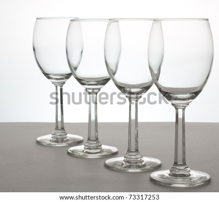 A row of 4 wine glasses at an angle - stock photo