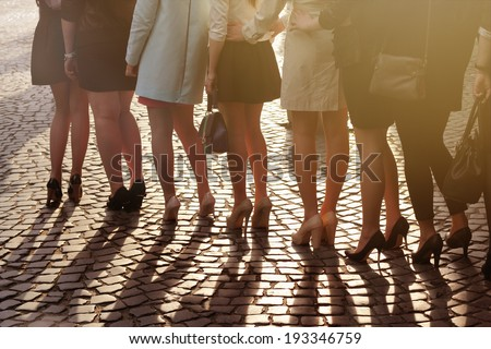 A row of young pretty women on high heels standing on block paving - stock photo
