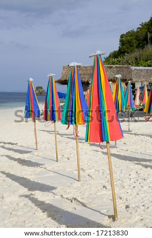 A row or colorful umbrellas on the beach - stock photo