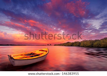 A rowboat watches an amazing sunset - stock photo