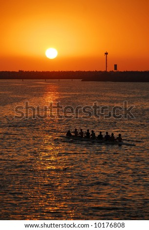 A rowing team returns from training during a golden sunset - stock photo