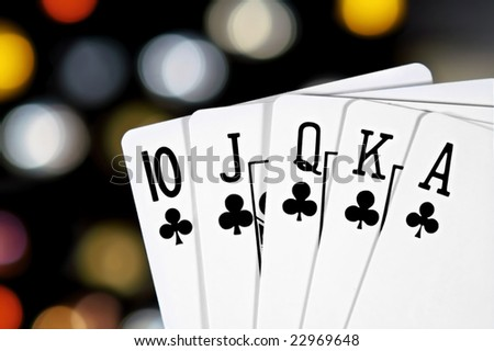 A royal flush, club suit, with colorful bokeh in the background. - stock photo