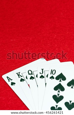 A Royal flush of spade cards poker hand on red background with copy space Royal flush, the best hand possible in poker.