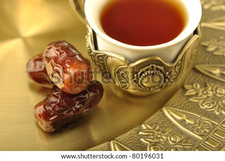 A royal, golden cup of tea with dates - stock photo