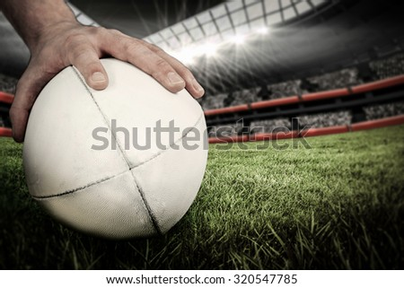 A rugby player posing a rugby ball against rugby stadium - stock photo