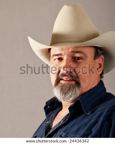 A rugged old cowboy takes a break from his busy day. - stock photo