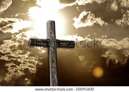 A rugged wooden cross against a bright sun and cloudy sky - sepia tone with intentional dramatic flare and chroma. - stock photo