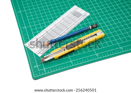 A ruler, cutter, cutting mat, pencil isolated over a white background - stock photo