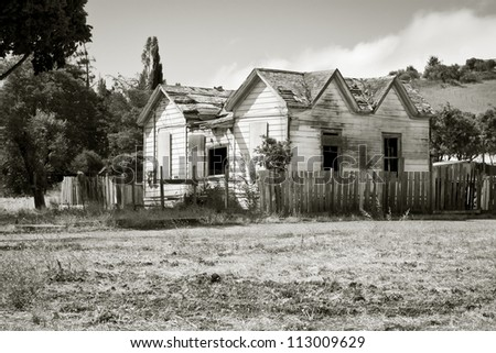 A run-down, vacant house in a field property.