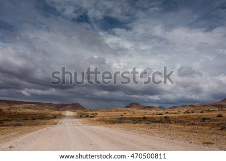 a rural dirt road leading to nowhere with dark stormy clouds above.
