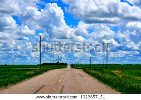 A rural highway in Saskatchewan Canada surrounded by lush green canola and wheat fields and a brilliant blue sky with puffy white clouds.