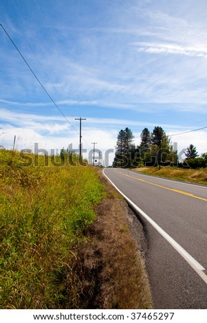 A rural highway travels up and over a hill with trees and blue sky.