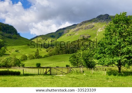 A rural landscape of green farm fields and country hillsides near Rosthwaite, England. - stock photo