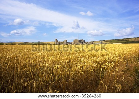 a rural landscape with golden wheat fields under a blue summer sky and a distant potash mine - stock photo