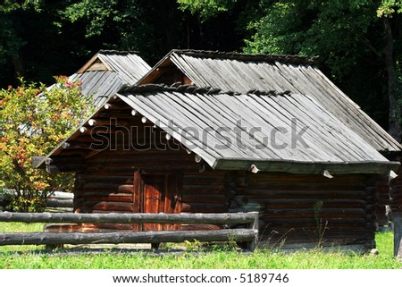 a rural log-house with wild ash tree - stock photo