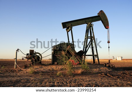 A rural pumpjack in operation in a farm field.