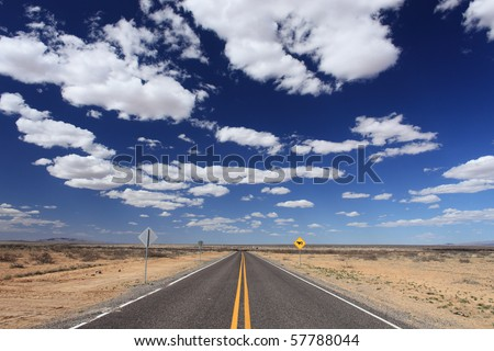 A rural road leading into the distance in southern New Mexico. - stock photo