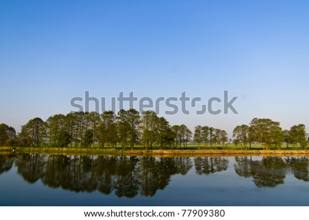 A rural small lake and a green forest