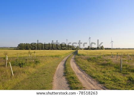 a rural wind farm with trees and a dusty track under a blue sky - stock photo