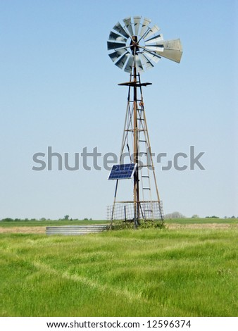 A rural windmill equipped with a solar power to store energy - stock photo
