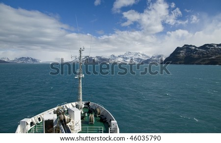 A Russian Icebreaker heading towards the beautiful snowy mountains of South Georgia on a sunny day. - stock photo