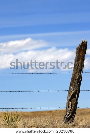 A rustic barbed-wire fence against an open sky in rural country - can represent boundaries or privacy, country life/values, wireless technology in rural communities, agriculture, etc. - stock photo