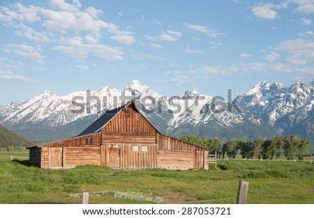 A rustic barn sits in front of the Grand Tetons near Jackson Hole, Wyoming. - stock photo