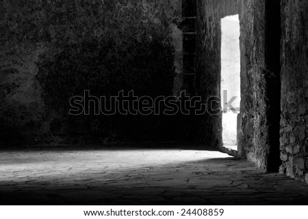a rustic hall with sunlight spilling through the door. - stock photo